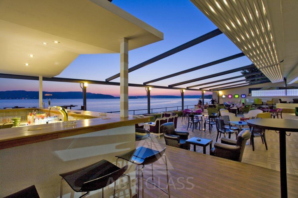 Terrasse de restaurant aménagée avec une Pergola sur mesure rétractable