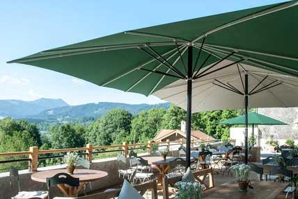 Terrasse de restaurant dans les Alpes équipée de parasols imperméables Festival