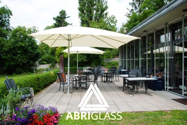 Parasol Exzentro protégeant une terrasse avec parc arboré