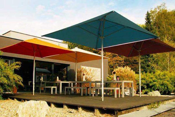 Plusieurs parasols BEACH en protection d'une terrasse bois
